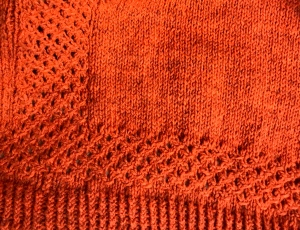 close up of knitted waistcoat showing textured wrap stitches, stockinette and twisted rib.