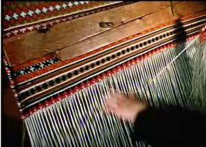 Screen shot from silent video showing the use of a warp weighted loom to produce a carpet.
