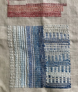 Close up of embroidered linen with a variety of blue and red stitches