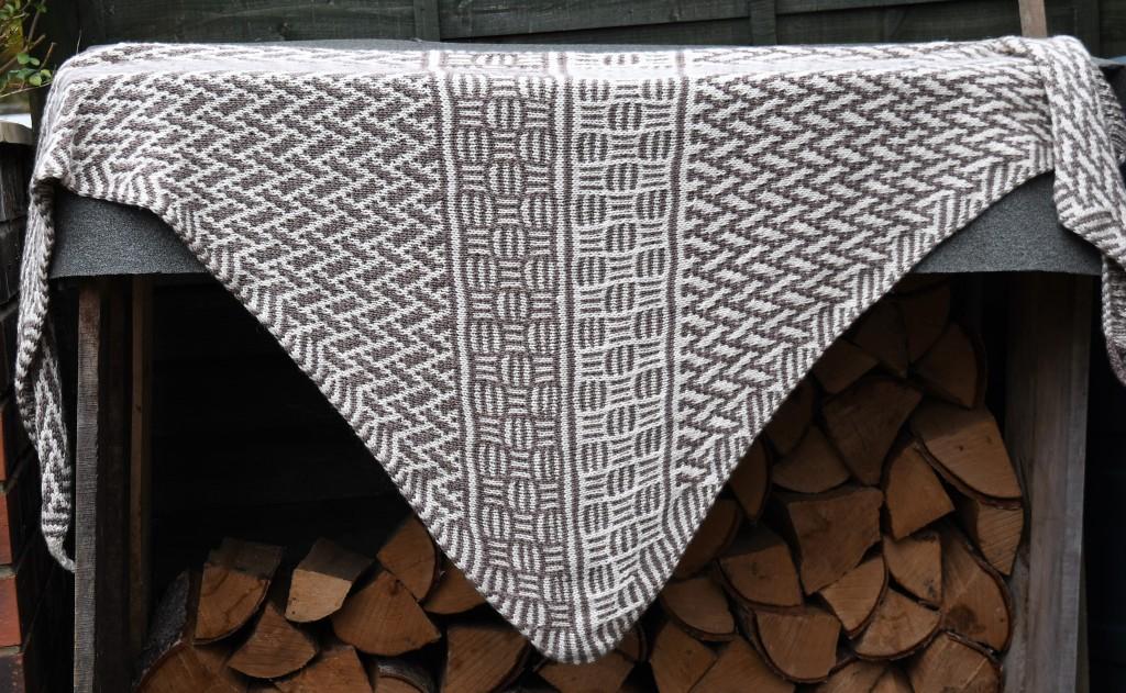 Counterchange shawl draped over a log store.
