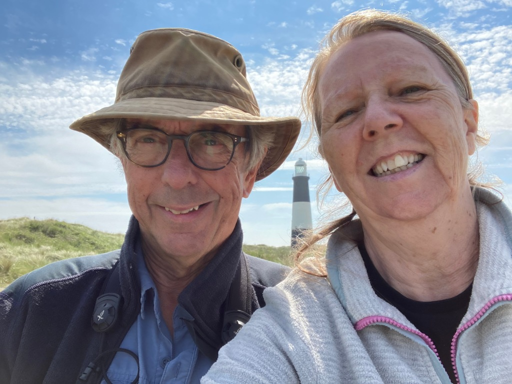 Two oldies enjoying the sunshine and the sea with a lighthouse in the background.